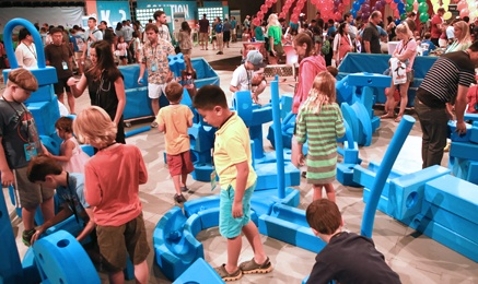 Math Fair floor, kids navigating big blocks as machinery.